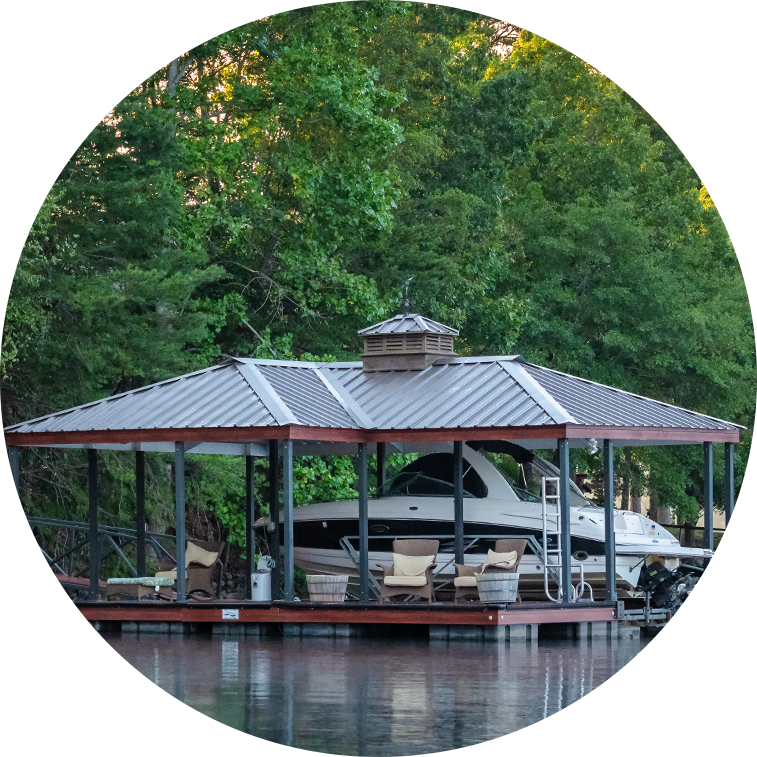 Boat dock built by Kroeger Marine on Lake Hartwell. Dark black roof with a large boat under the dock.