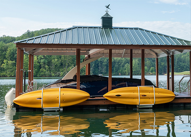 two yellow kayaks stored on a dock in the lake with a green metal roof