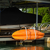 orange kayak stored next to a boat on a dock