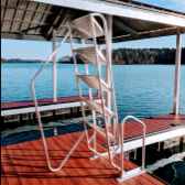 a dock with a ladder pointing in the air. Dock has red wood with lake in the background