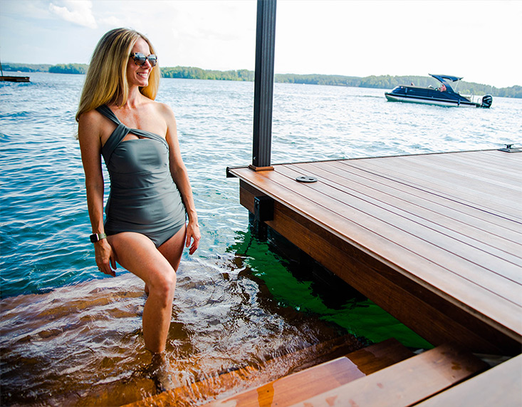 woman standing on the stairs of a dock in the lake